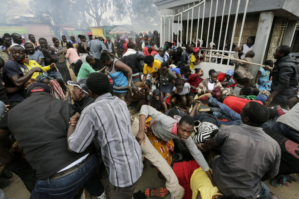 Residents desperate for a planned distribution of food for those suffering under Kenya's coronavirus-related movement restrictions push through a gate...