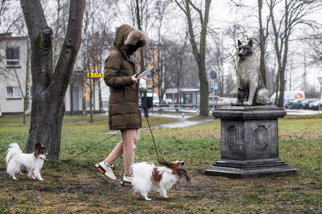 A woman walks with her dogs past the statue of the stray dog Zorik, warming up a kitten, is placed in front of a shopping center in Tallinn, Estonia, ...
