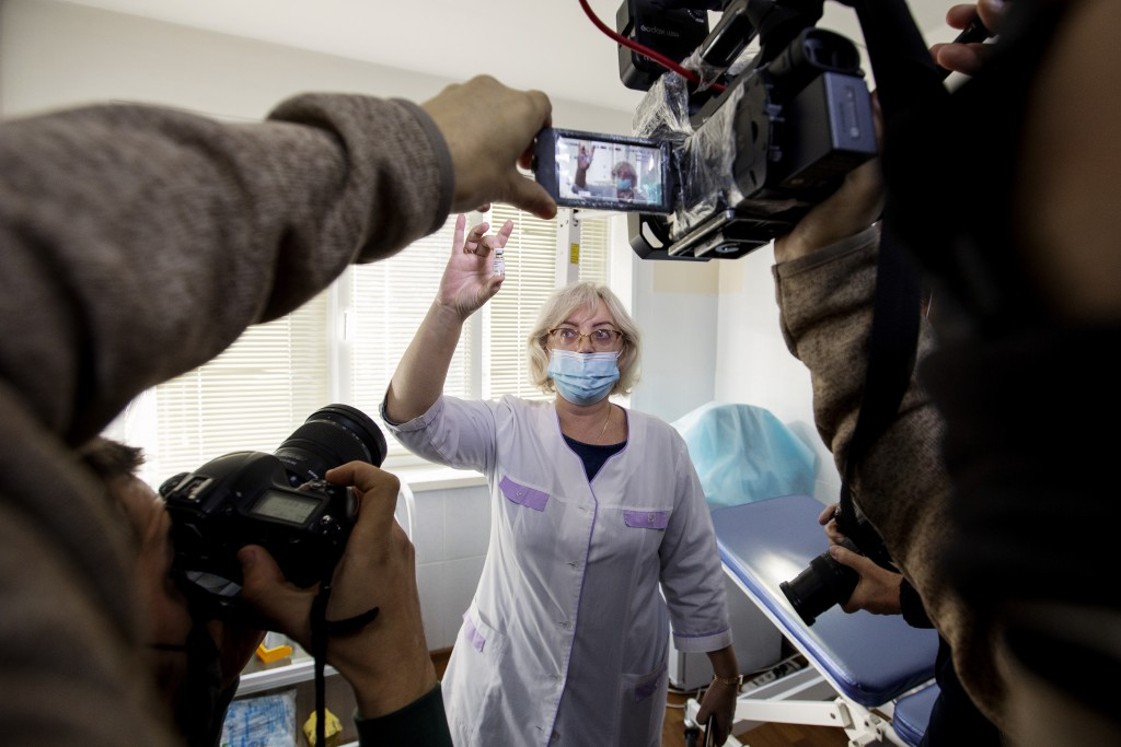 A Russian medical worker, center, shows a vial with Russia's Sputnik V coronavirus vaccine to the media prior to a shot in a hospital in Vladivostok, ...