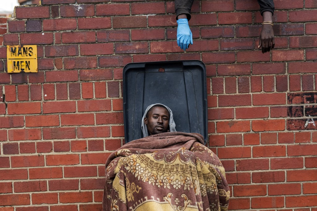 Henry sits in a trash bin as he and other homeless people rest at the Caledonian stadium in downtown Pretoria, South Africa, Thursday April 2, 2020, a...
