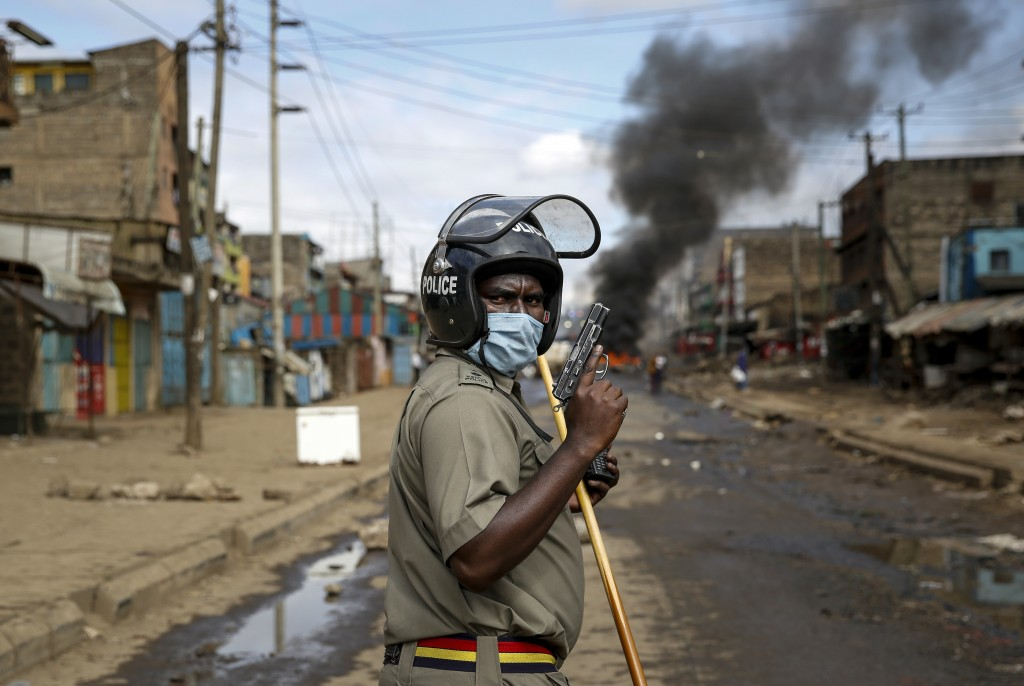 A police officer holds a pistol during clashes with protesters near a burning tyre barricade in the Kariobangi slum of Nairobi, Kenya Friday, May 8, 2...