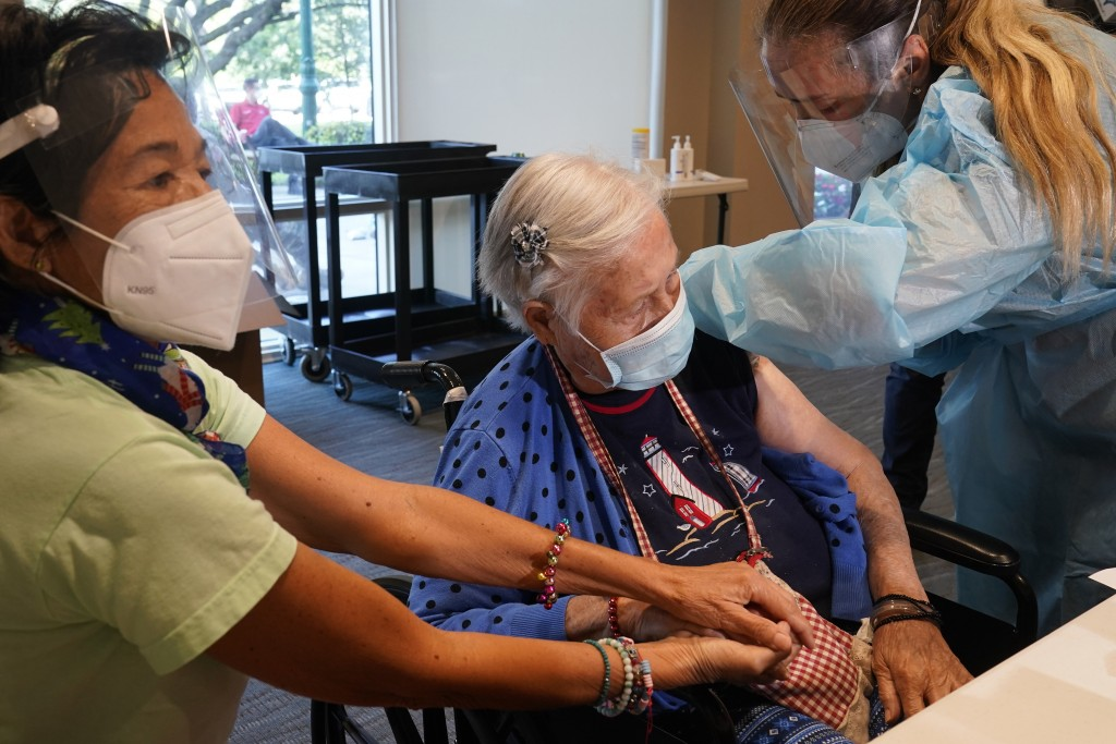 Patricia Wasseman, holds Hermina Levin's hands as nurse Eva Diaz administers the Pfizer vaccine at John Knox Village, Wednesday, Dec. 16, 2020, in Pom...