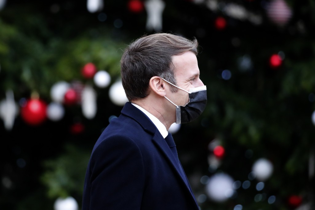 French President Emmanuel Macron walks in the courtyard of the Elysee Palace as he meets Portuguese Prime Minister Antonio Costa, Wednesday, Dec. 16, ...
