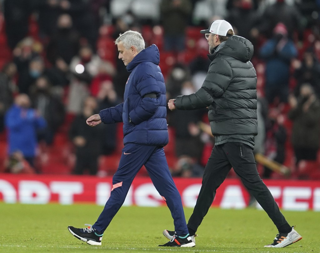 Tottenham's manager Jose Mourinho, left and Liverpool's manager Jurgen Klopp walks onto the pitch after the end of the English Premier League soccer m...