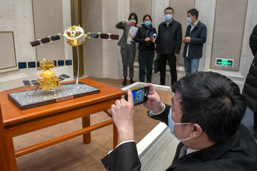 People wearing face masks to prevent the spread of the coronavirus take photos of a model of China's Chang'e 5 lunar orbiter and lander before a press...