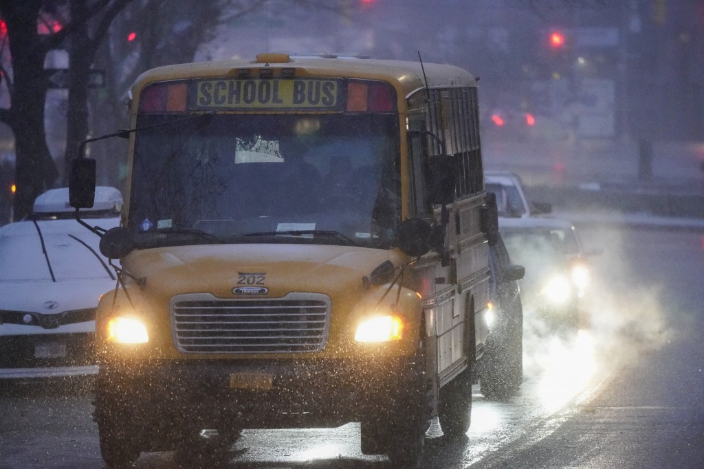 A school bus moves after dropping off students in the Queens borough of New York as snow starts to fall, Wednesday, Dec. 16, 2020. (AP Photo/Frank Fra...