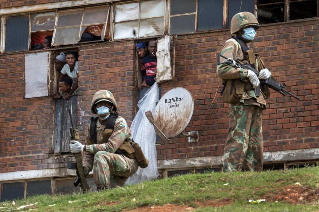 South African National Defense Forces patrol the Men's Hostel in the densely populated Alexandra township east of Johannesburg, March 28, 2020, enforc...