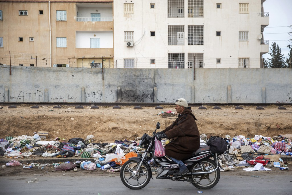 A man rides his motorcycle in front of garbage in Kasserine, Tunisia, on Friday Dec. 11, 2020. Hundreds of desperate Tunisians have set themselves on ...