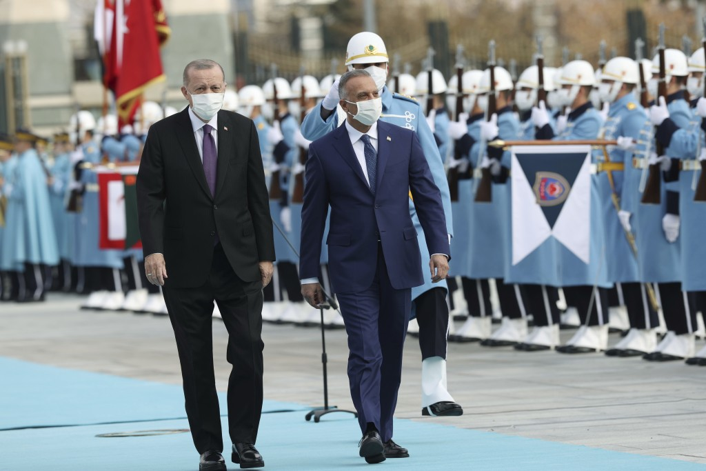 Turkey's President Recep Tayyip Erdogan, left, walks with Iraqi Prime Minister Mustafa al-Kadhimi, centre, as they review an honour guard during a wel...