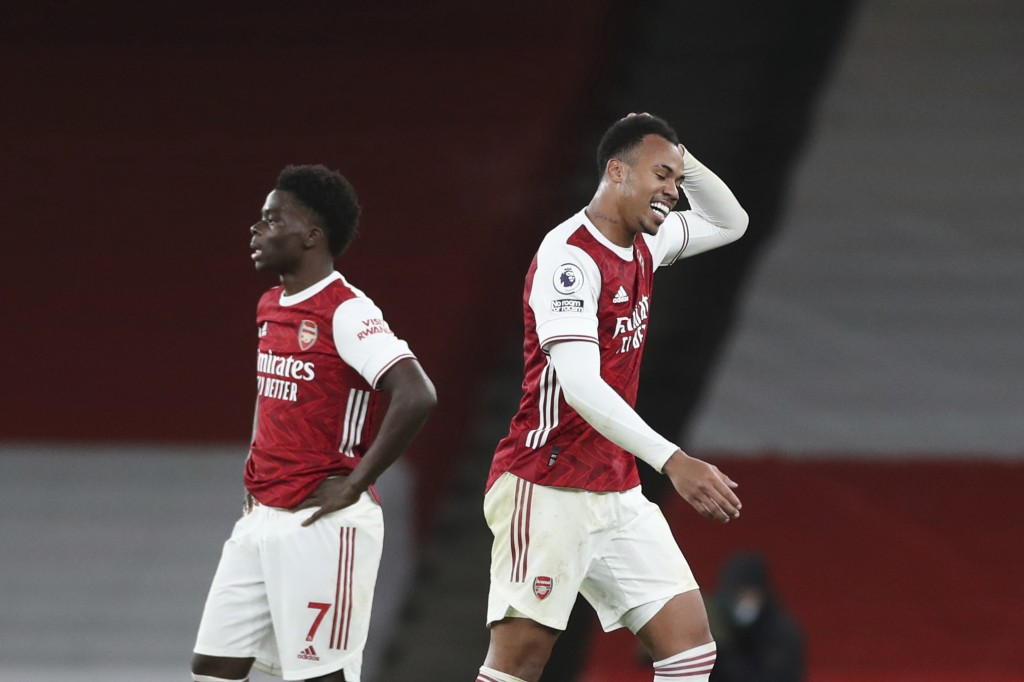 Arsenal's Gabriel, right, leaves the pitch after being sent off for a foul on Southampton's Theo Walcott, bottom, during an English Premier League soc...