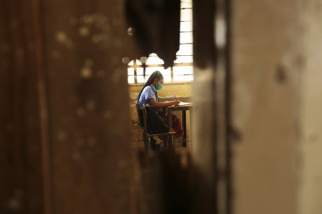 A student takes notes inside a classroom at a school in Harare, Monday, Sept, 28, 2020. Zimbabwe schools have reopened in phases, but with smaller num...