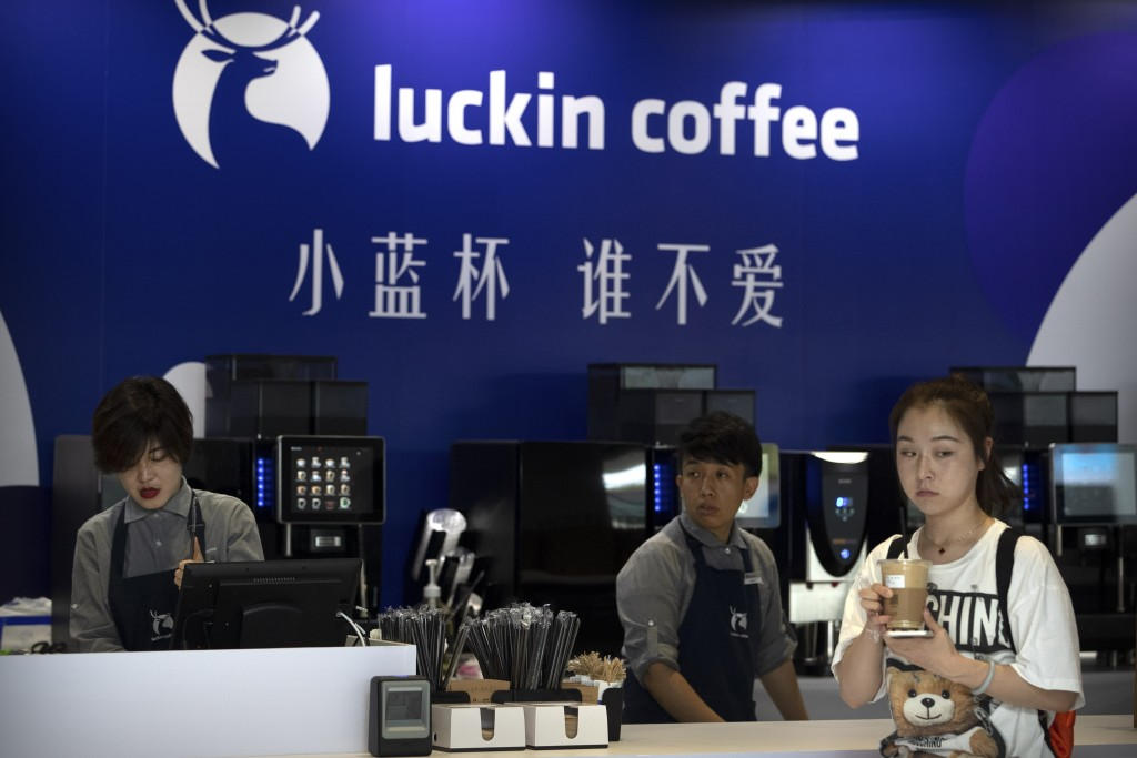 FILE - In this Aug. 15, 2018, file photo, a customer picks up her order from a Luckin Coffee pop-up shop at the World Robot Conference in Beijing. Chi...
