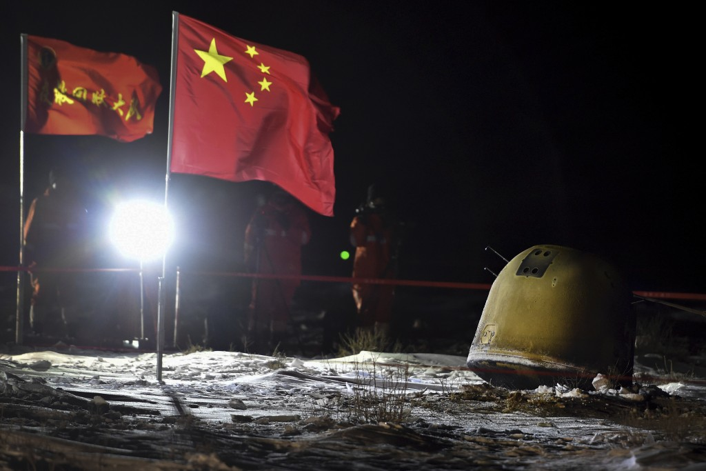 In this photo released by Xinhua News Agency, recovery crew members film the capsule of the Chang'e 5 probe after its successful landed in Siziwang di...