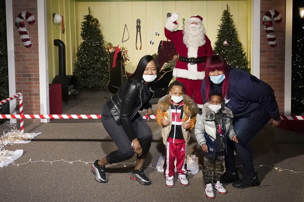 The Bell family poses for a photo with a social distant Santa as they visit Santa's Garage on the roof of a parking deck near Soldier Field in Chicago...