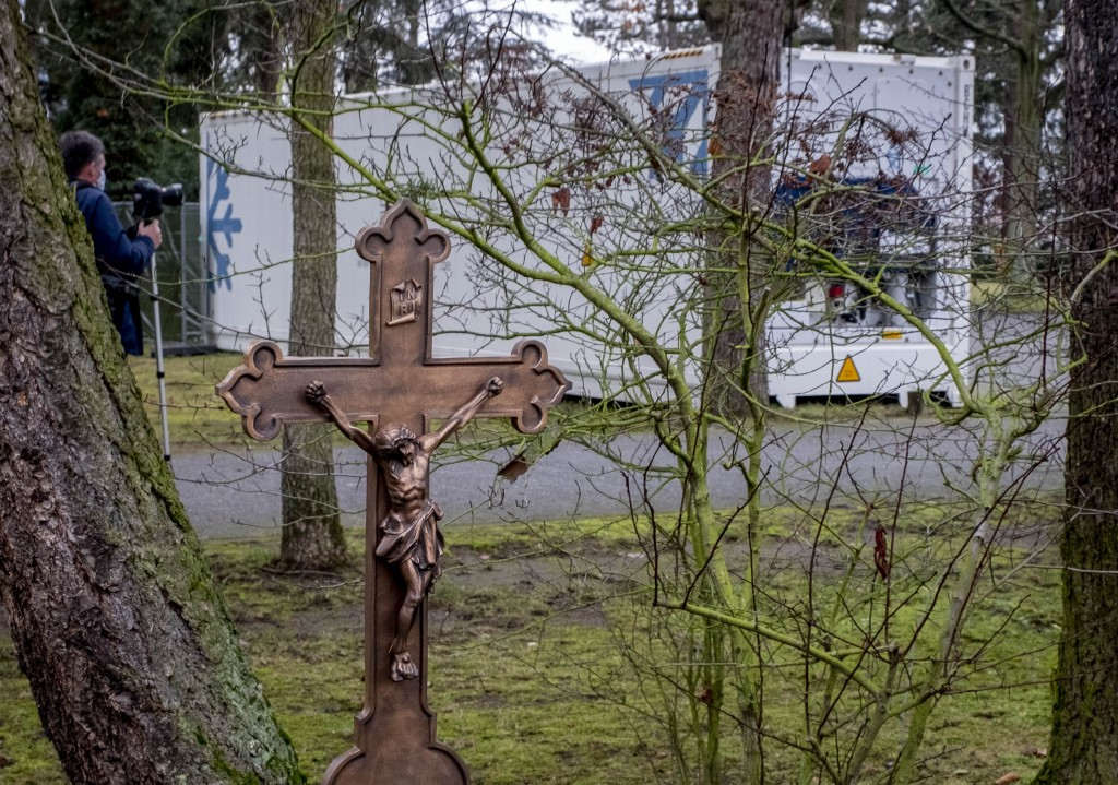 A cross is seen near a refrigeration container storing Covid-19 victims on the cemetery in Hanau near Frankfurt, Germany, Thursday, Dec. 17, 2020. The...