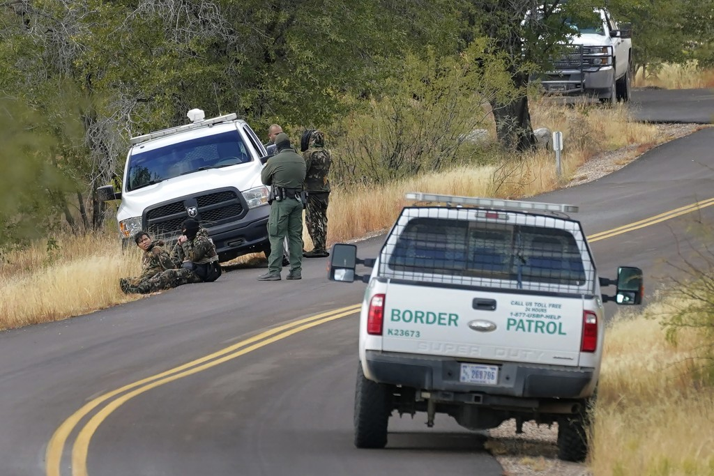 A pair of Customs and Border Patrol agents detain three migrants leading up to Montezuma's Pass in Coronado National Memorial, Thursday, Dec. 10, 2020...