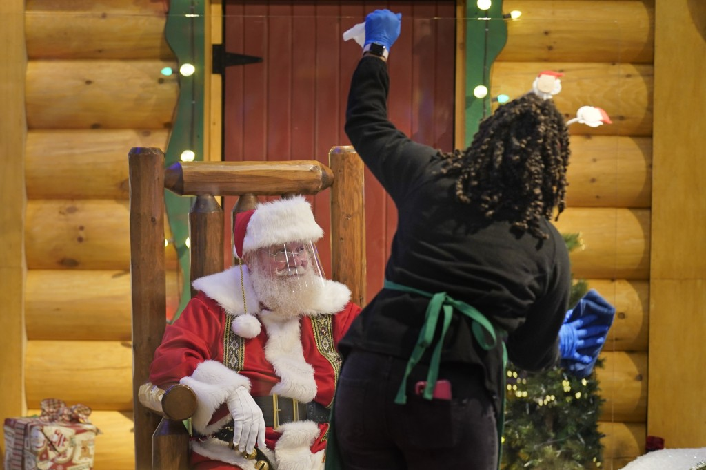 LaToya Booker cleans a transparent barrier between visitors for Santa at a Bass Pro Shop in Bridgeport, Conn., on Nov. 10, 2020. In this socially dist...
