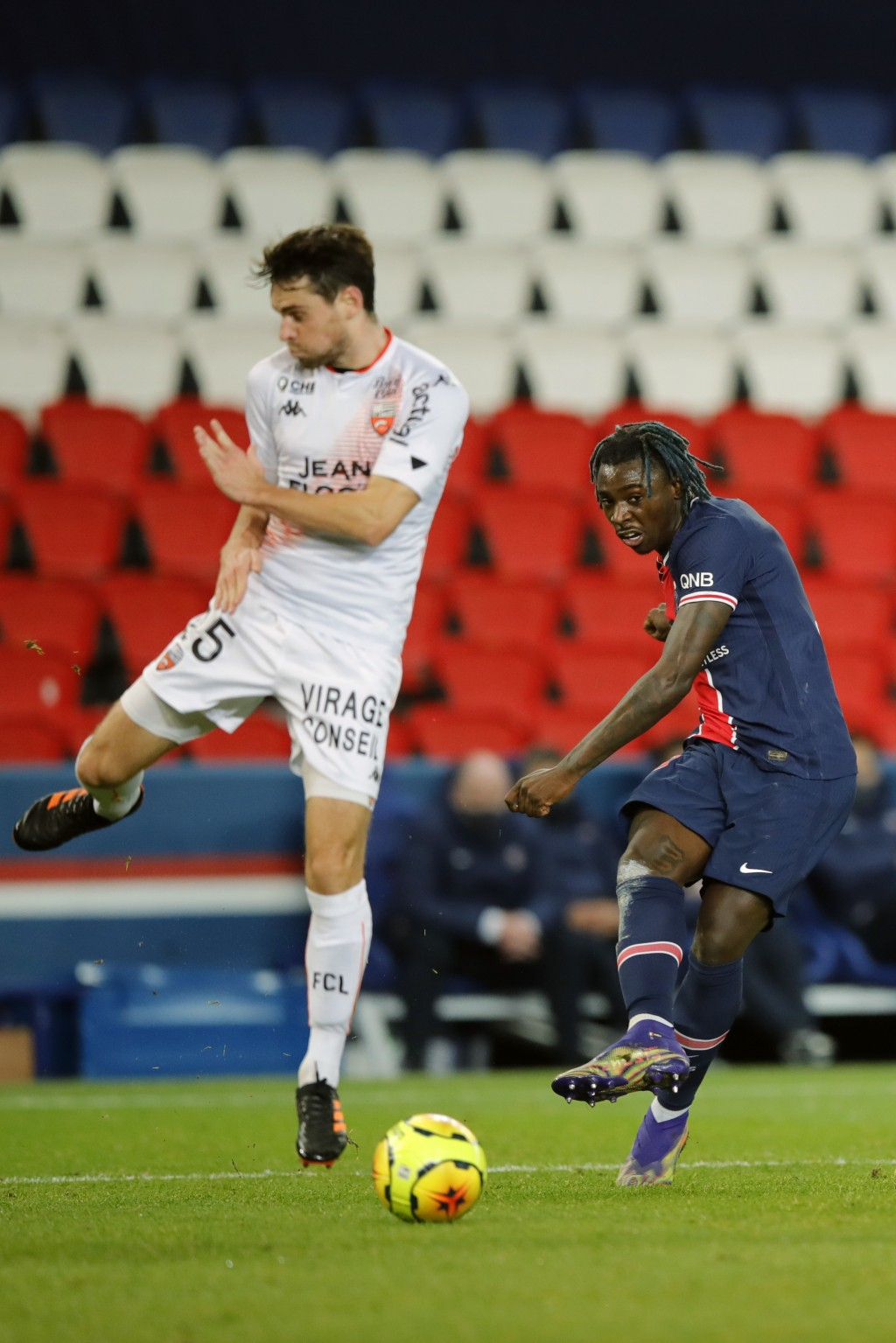 PSG's Moise Kean, right, kicks the ball past Lorient's Vincent Le Goff during the French League One soccer match between Paris Saint-Germain and Lorie...