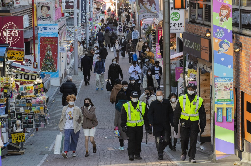 People wearing face masks walk through a famed shopping street in the Harajuku neighborhood in Tokyo on Thursday, Dec. 17, 2020. The Japanese capital ...
