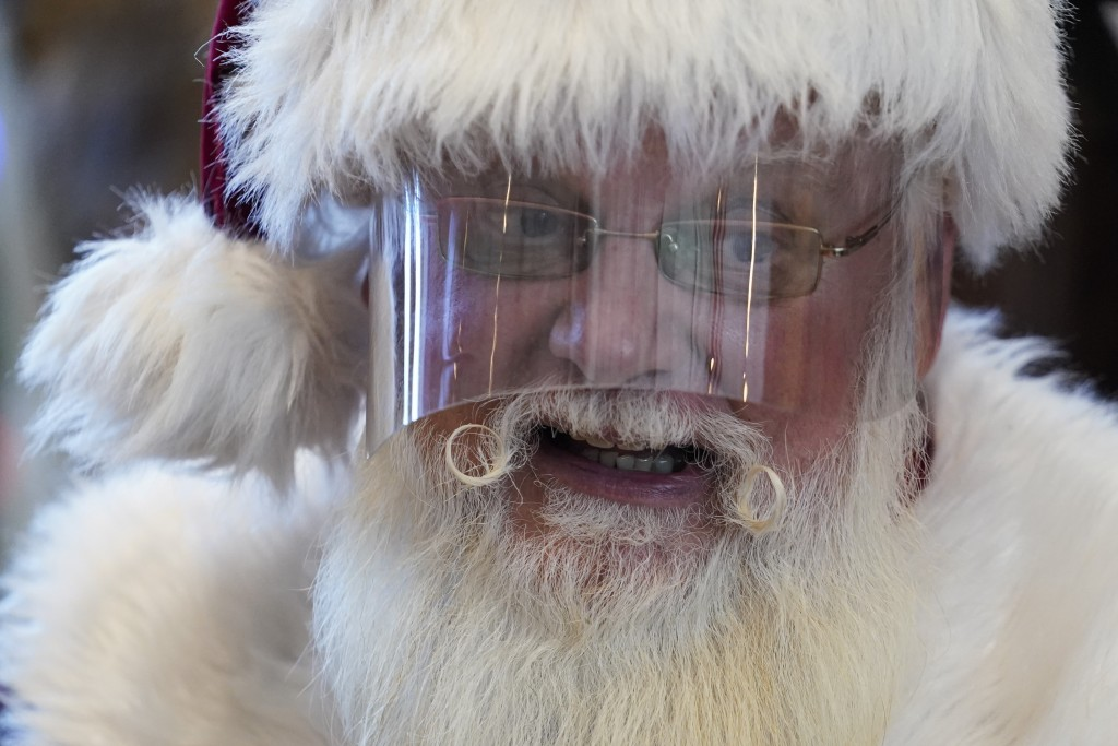 Santa Claus wears a face shield while visiting with children at Bass Pro Shop in Rancho Cucamonga, Calif., on Dec. 4, 2020. In this socially distant h...