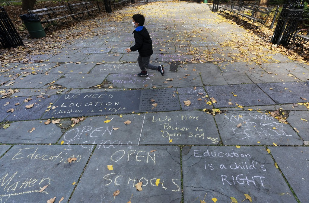FILE - A child runs across a sidewalk in front of New York's City Hall decorated with graffiti in favor of keeping open public schools, Thursday, Nov....