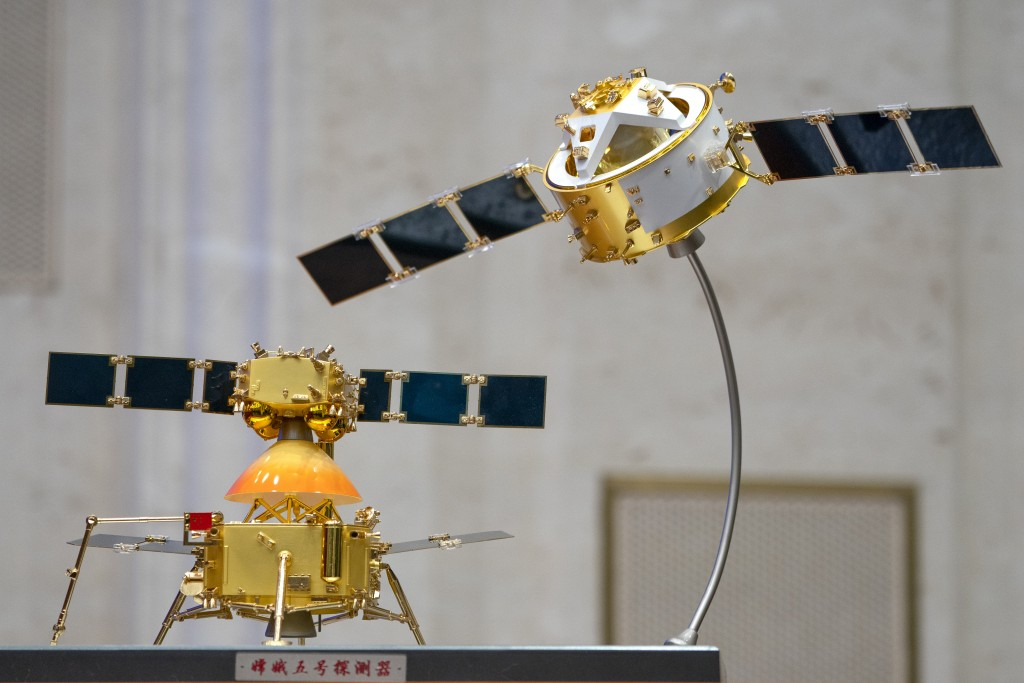 A model of China's Chang'e 5 lunar orbiter and lander are displayed before a press conference at the State Council Information Office in Beijing, Thur...