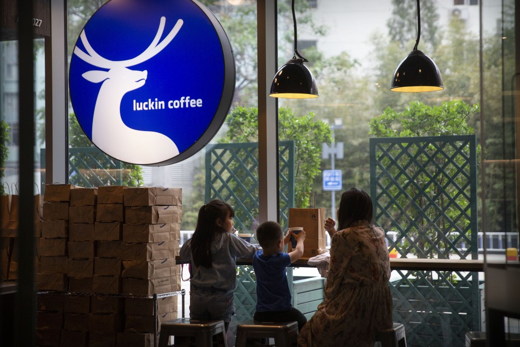 FILE - In this May 18, 2019, file photo, customers sit inside a Luckin Coffee shop at a shopping center in Beijing. China's Luckin Coffee has agreed t...