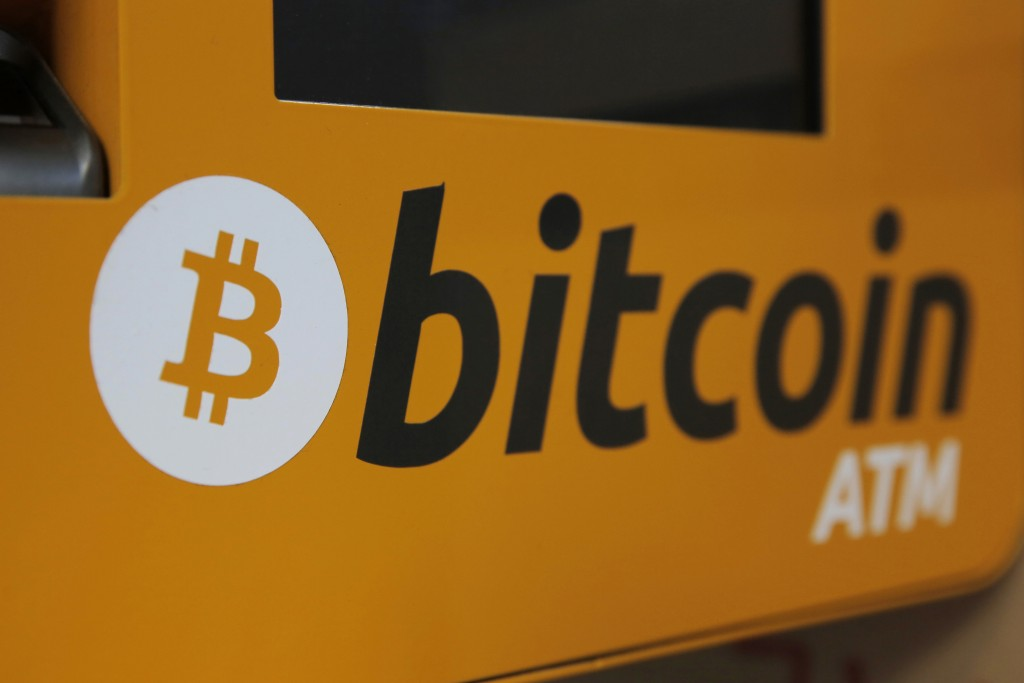FILE- In this Dec. 21, 2017, file photo, a Bitcoin logo is shown is displayed on an ATM in Hong Kong. The price of bitcoin rose above $20,000 for the ...