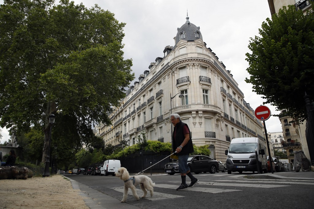FILE - In this Aug.13, 2019 file photo, a man walks his dog next to an apartment building owned by Jeffrey Epstein in Paris. Modeling agent Jean-Luc B...