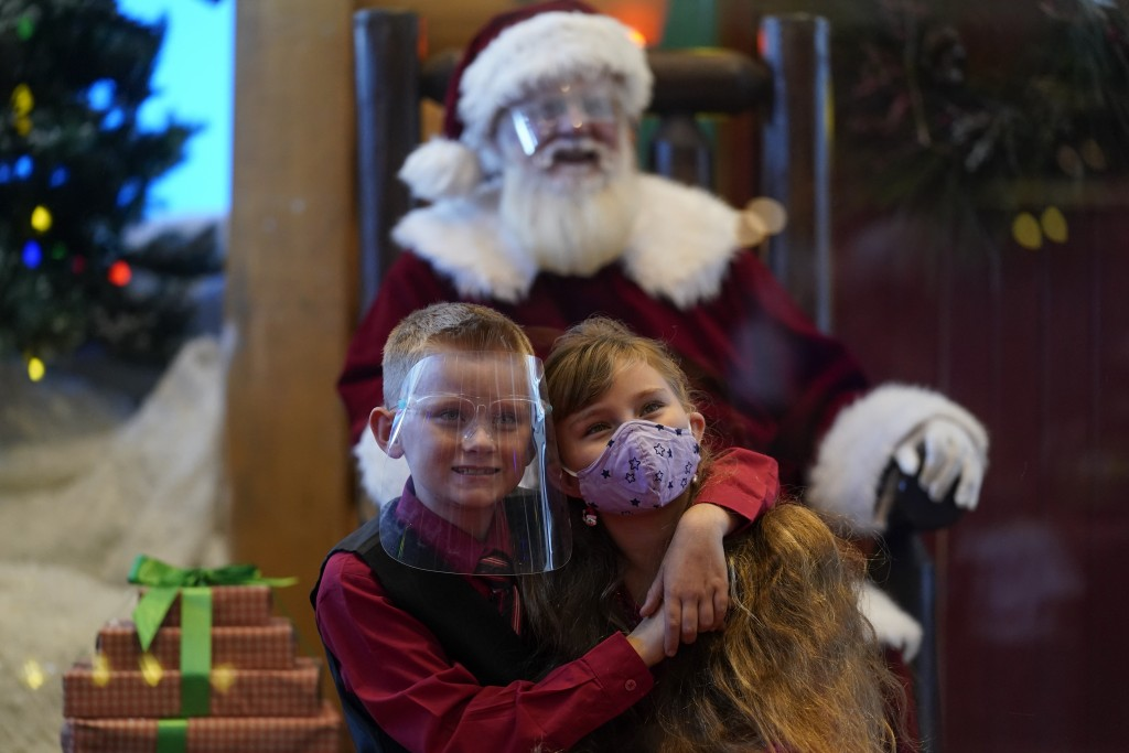 William Peargin, left, and Payton Peargin, right, both 8, pose for a socially distant photo with Santa Claus, who sits behind a sheet of plexiglass, a...