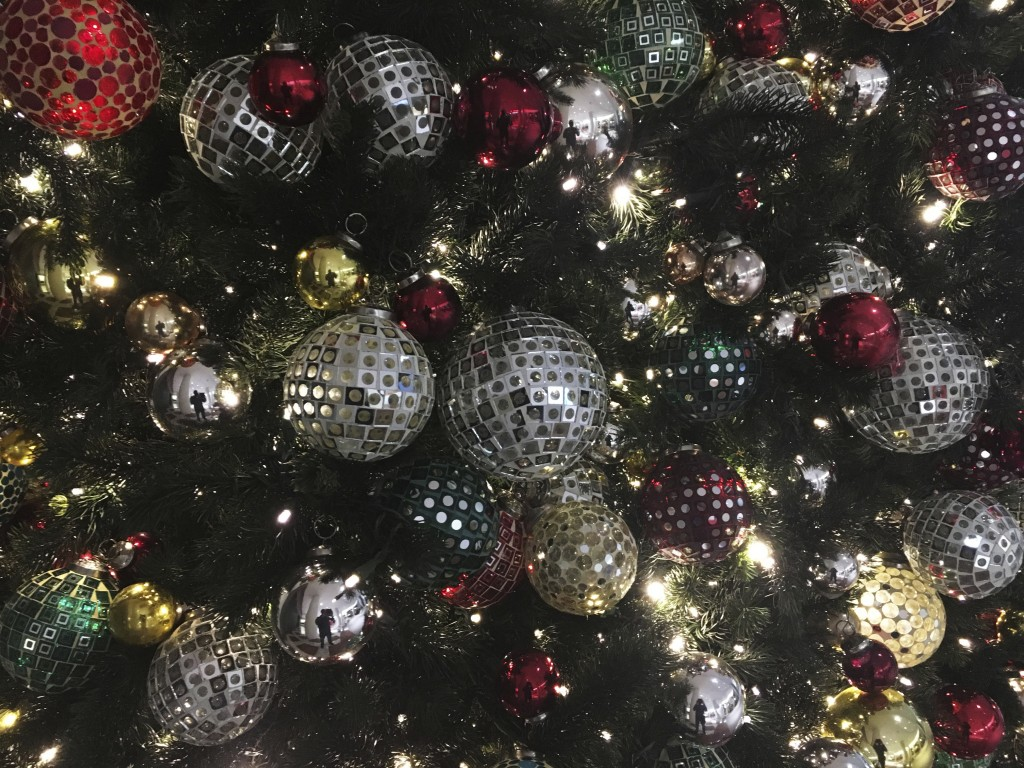 FILE - In this Friday, Dec. 1, 2017, file photo, ornaments hang on a Christmas tree on display in New York. Office holiday parties are tricky in 2020 ...