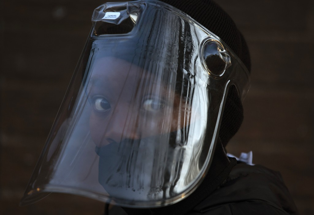 A student, wearing a face mask and shield to protect against the spread of COVID-19, returns to the Melpark Primary School in Johannesburg, Monday Aug...