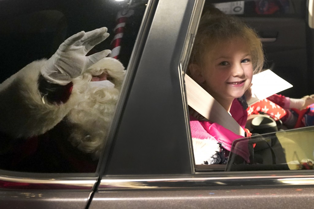 Brynn Brennan smiles at a social distant Santa as she rides past Santa's Garage on the roof of a parking garage next to Soldier Field in Chicago on De...