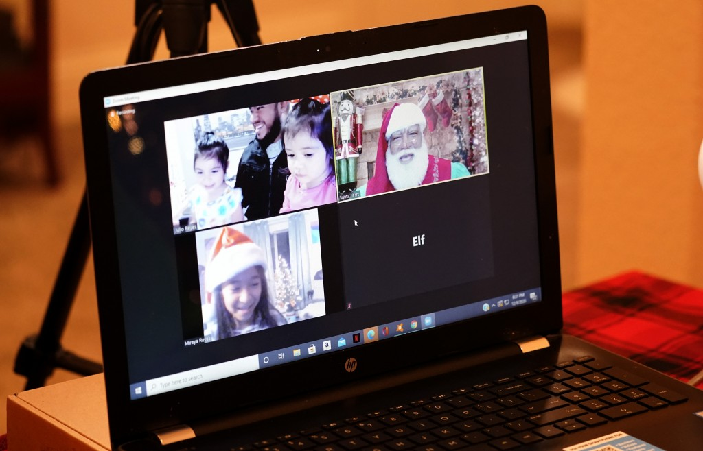 Larry Jefferson, right, portrays Santa Claus and conducts a visit via a computer screen with Raquel Anaya, bottom left, and her cousins Lexi Reyes, to...