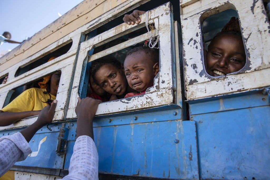 Tigray refugees who fled the conflict in the Ethiopia's Tigray ride a bus going to the Village 8 temporary shelter, near the Sudan-Ethiopia border, in...