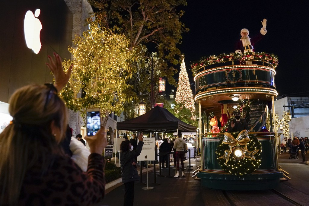 Santa Claus waves to shoppers from a safe distance at the top level of a trolly at The Grove shopping center in Los Angeles on Dec. 3, 2020. Santa vis...