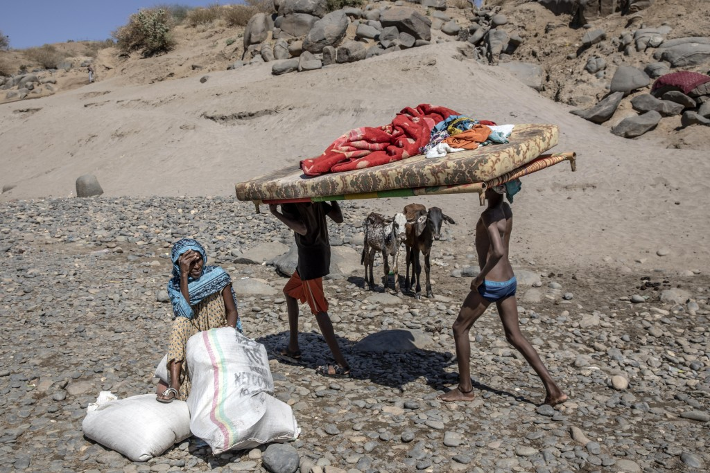 Tigray refugees who fled the conflict in the Ethiopia's Tigray carry their furniture on the banks of the Tekeze River on the Sudan-Ethiopia border, in...
