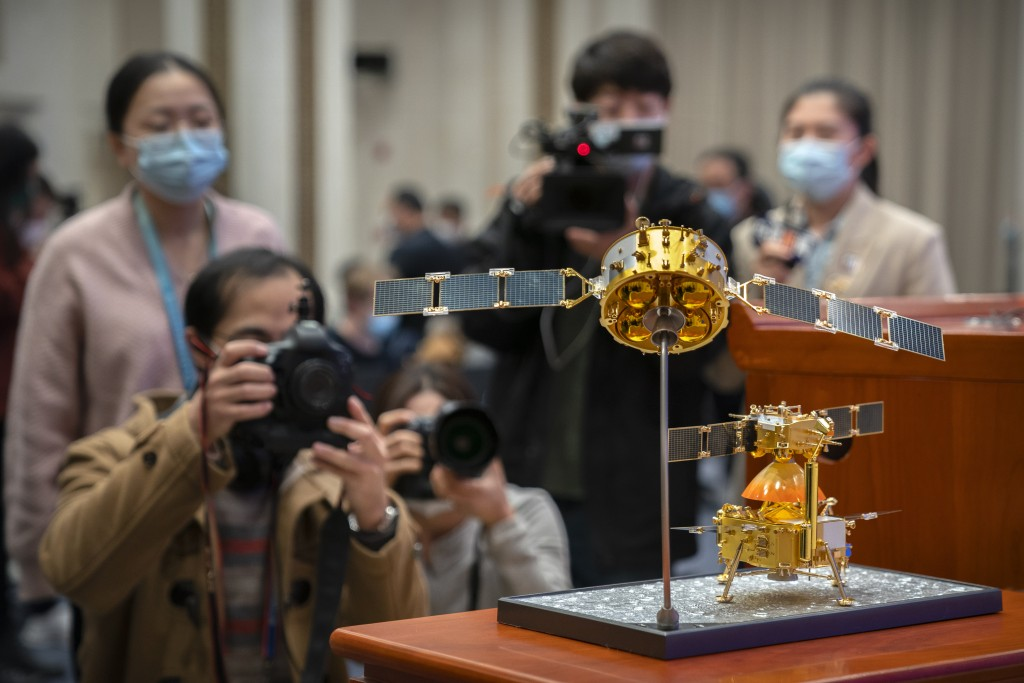 Journalists wearing face masks to prevent the spread of the coronavirus take photos of a model of China's Chang'e 5 lunar orbiter and lander before a ...