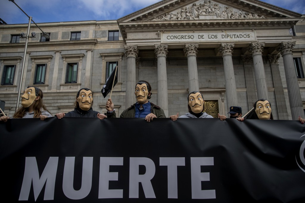 "People hold a banner reading in Spanish ""Death"" as they protest against a law to legalize euthanasia, in front of the Spanish Parliament in Madrid, Sp..."