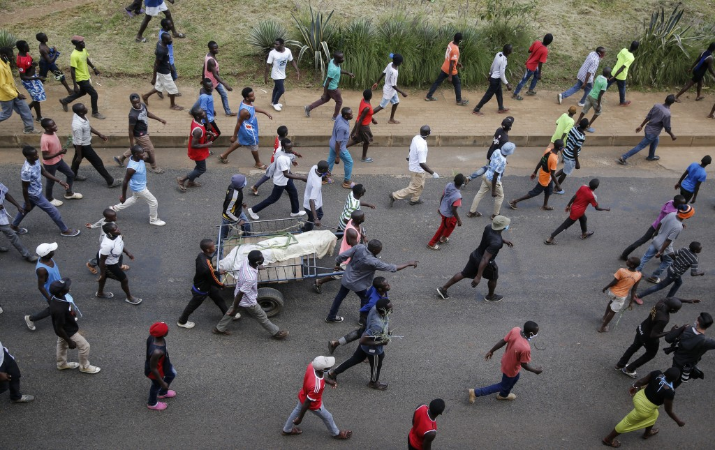 Residents protest with the covered dead body of a man, who they claimed had been beaten by police for being outside during the dusk to dawn curfew, bu...