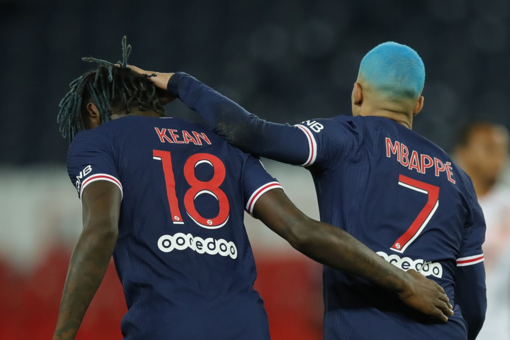 PSG's Kylian Mbappe, right celebrates with PSG's Moise Kean after scoring during the French League One soccer match between Paris Saint-Germain and Lo...