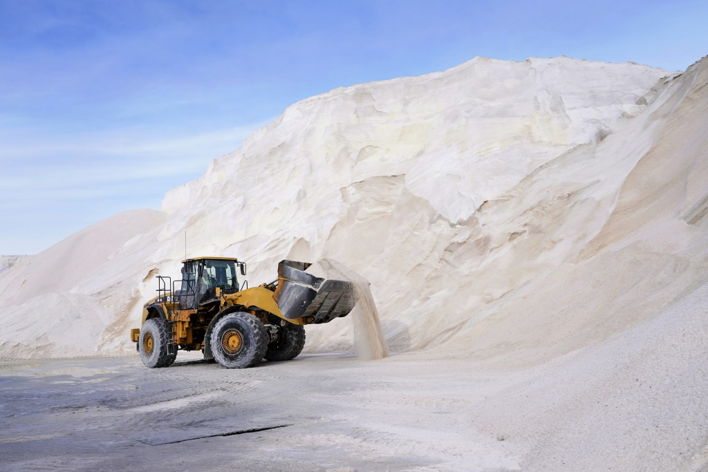 A front loader works at a large pile of road salt, Wednesday, Dec. 16, 2020, in Chelsea, Mass., as preparation continues for a storm that is expected ...