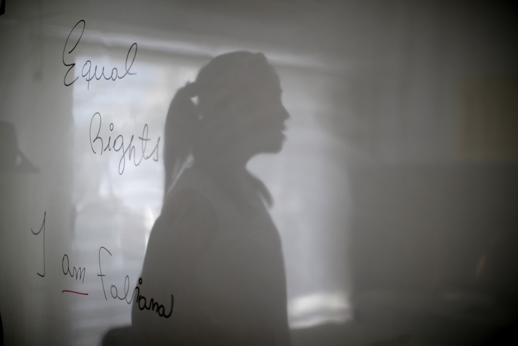 """Transgender woman Fabiana Rodríguez, an English teacher, poses for a portrait with her shadow overlaying the message she wrote on her blackboard: """"Equ..."""