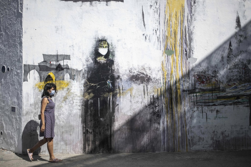 A woman wearing a face mask to prevent the spread of coronavirus walks past a mural of a mask-wearing Mona Lisa, in the Medina of Asilah, northern Mor...