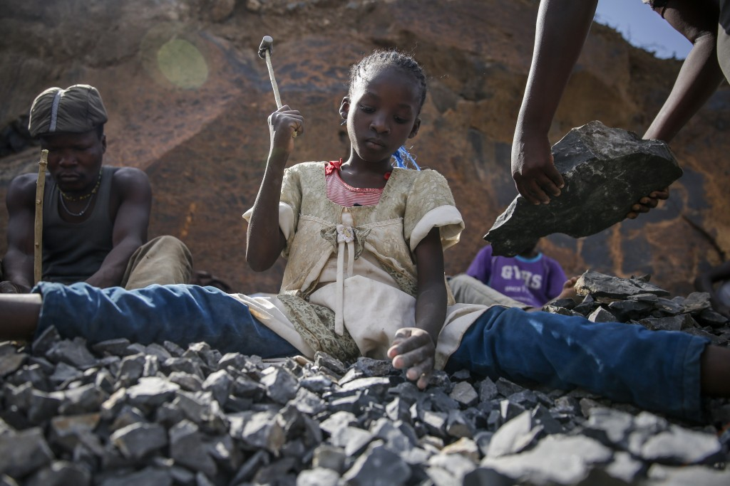 Irene Wanzila, 10, works breaking rocks with a hammer along with her younger brother, older sister and mother, who says she was left without a choice ...