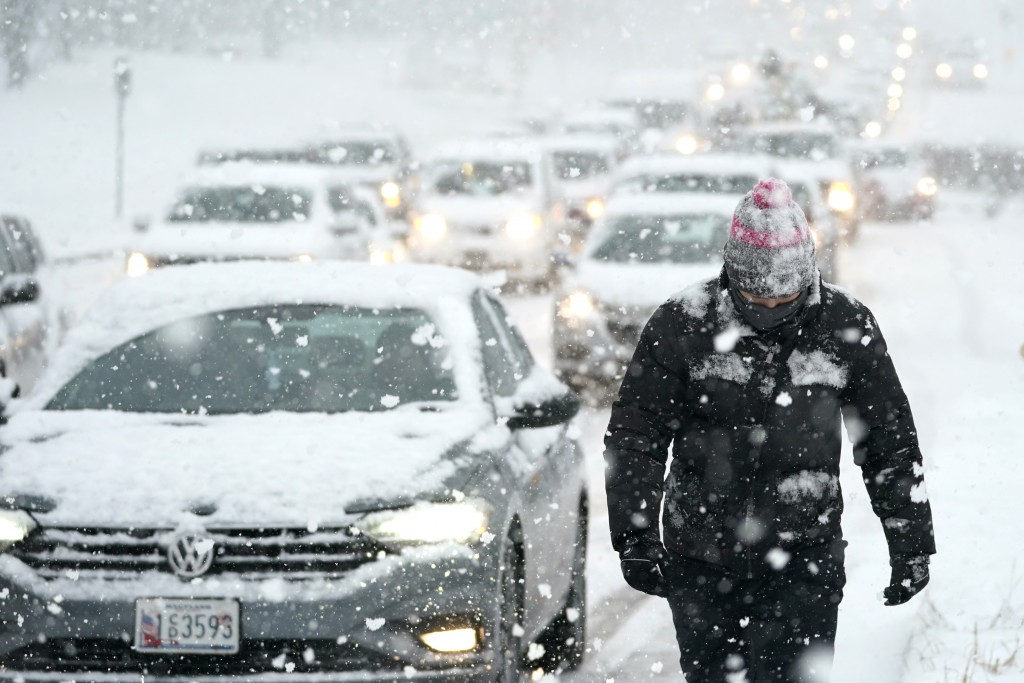 Miguel Reider walks near a traffic jam caused by vehicles stuck on a hill during a snowstorm, Wednesday, Dec. 16, 2020, in Towson, Md. Reider and frie...