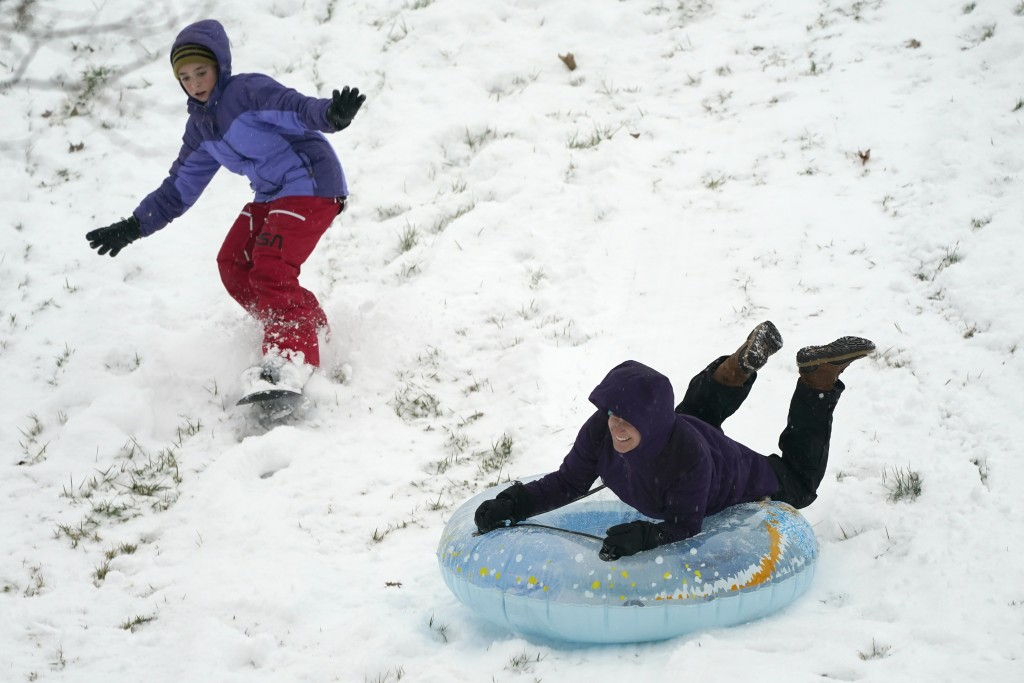 Krystal Krause, right, rides a tube and Lilyann Richard, 11, snowboards down a hill during a snowstorm, Wednesday, Dec. 16, 2020, in Lutherville-Timon...