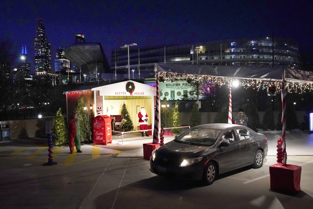 A car drives through Santa's Garage past the social distant Santa, on the roof of a parking garage next to Soldier Field and a backdrop of the Chicago...