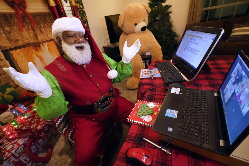 Larry Jefferson portrays Santa Claus and conducts a visit via a computer screen with Raquel Anaya and her cousins Lexi and Luna Reyes from his home in...