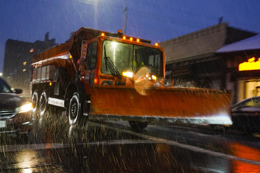 A sanitation truck fitted with a plow treats Lefferts Boulevard in the Queens borough of New York as snow starts to fall, Wednesday, Dec. 16, 2020. (A...